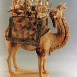 A Tang-triple-color ceramic camel that carries a small musical band on its back with a female performer standing in the middle singing and dancing